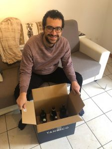 Luca sits on a cream sofa and in front of him is a box with six bottles of wine in it